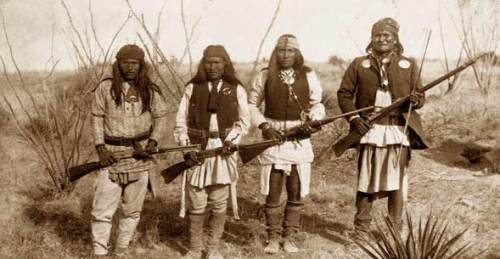 Apache warriors, armed and ready to fight, with Geronimo on right.